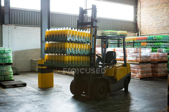 Empilement de bouteilles de jus emballées et chariot élévateur dans l'entrepôt de distribution — Photo de stock