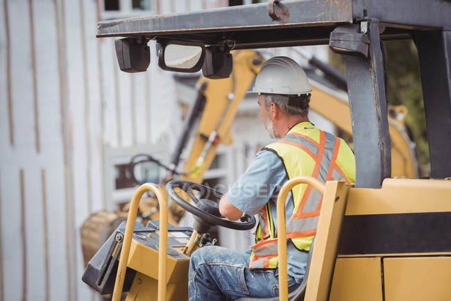 Homem operando bulldozer no canteiro de obras — Fotografia de Stock