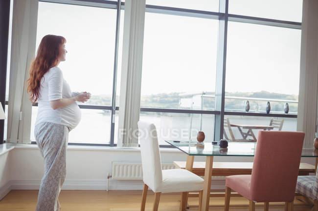 Вдумливий вагітна жінка тримає миску салат вдома — стокове фото