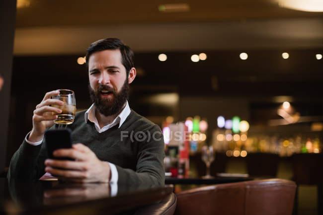 Людина, маючи чарки напоями під час використання мобільного телефону в м. бар — стокове фото