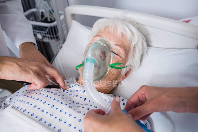 Médicos examinando a paciente mayor con estetoscopio en cama de hospital - foto de stock