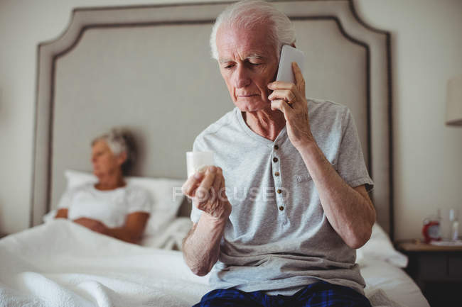 Worried senior man sitting in bedroom holding medicine and talking on mobile phone — Stock Photo