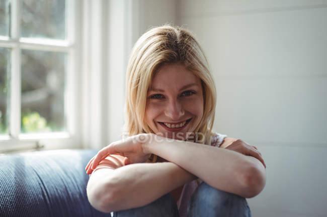 Портрет счастливой женщины, сидящей на диване в гостиной — стоковое фото