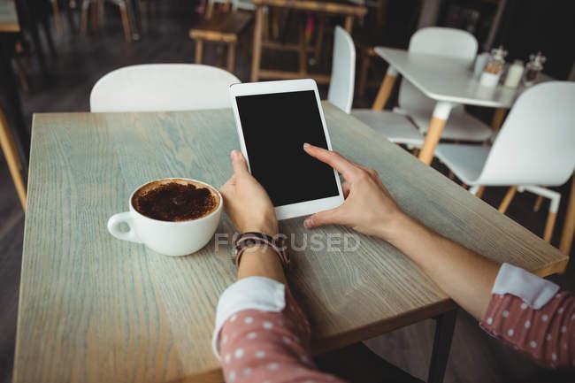 Mano de mujer usando tableta digital en la cafetería - foto de stock