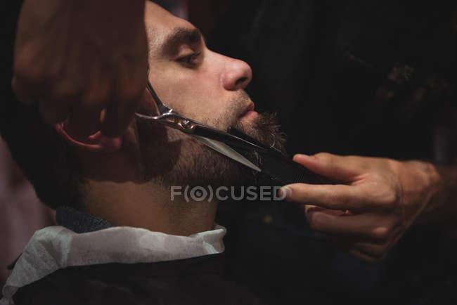 Uomo che si fa tagliare la barba con le forbici in barbiere — Foto stock