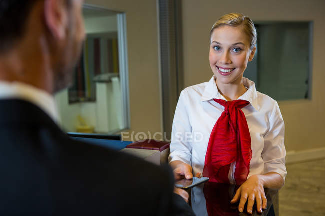 Female staff giving boarding pass to the businessman at the check in desk — Stock Photo