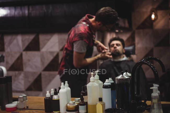 Riflessione dell'uomo che si fa tagliare la barba con le forbici nel negozio di barbiere — Foto stock