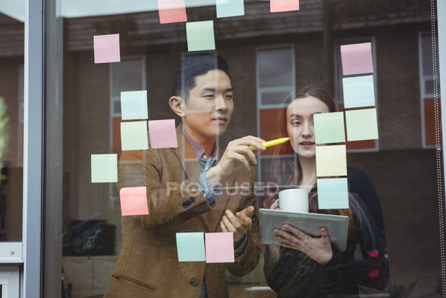 Business executives discussing over sticky notes in office — Stock Photo