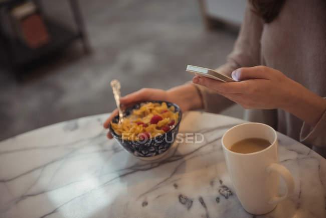 Close-up de mulher usando telefone celular enquanto toma café da manhã em casa — Fotografia de Stock
