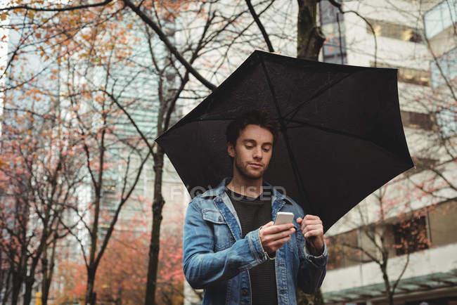 Homme utilisant un téléphone portable et tenant un parapluie dans la rue — Photo de stock