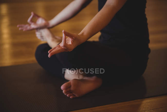 Cropped view of practicing woman doing mudra on yoga mat in fitness studio — Stock Photo