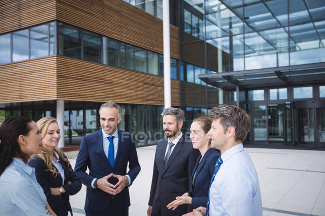 Group of businesspeople interacting outside office building — Stock Photo