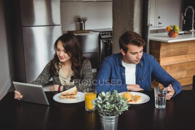 Couple utilisant tablette numérique et téléphone portable tout en prenant le petit déjeuner à la maison — Photo de stock