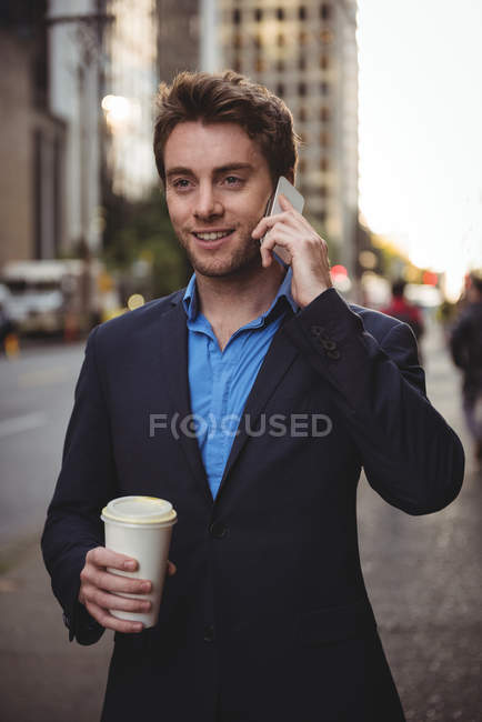 Businessman talking on mobile phone and holding coffee on street — Stock Photo