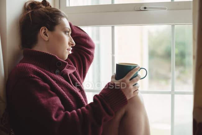 Задумчивая женщина сидит на подоконнике и держит чашку кофе дома — стоковое фото