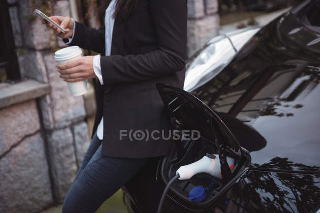 Woman using mobile phone while charging electric car at electric vehicle charging station — Stock Photo