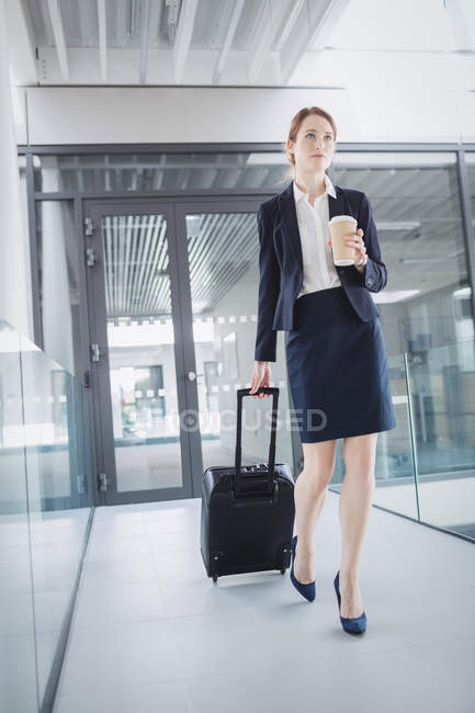 Businesswoman holding suitcase walking through office corridor — Stock Photo