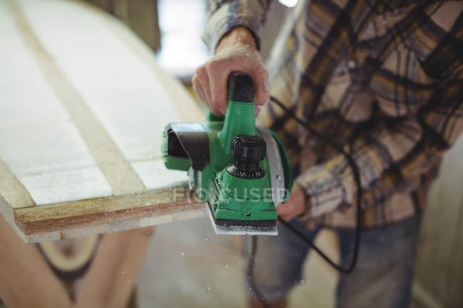 Mid-section of man using modified planer in the surfboard workshop — стоковое фото