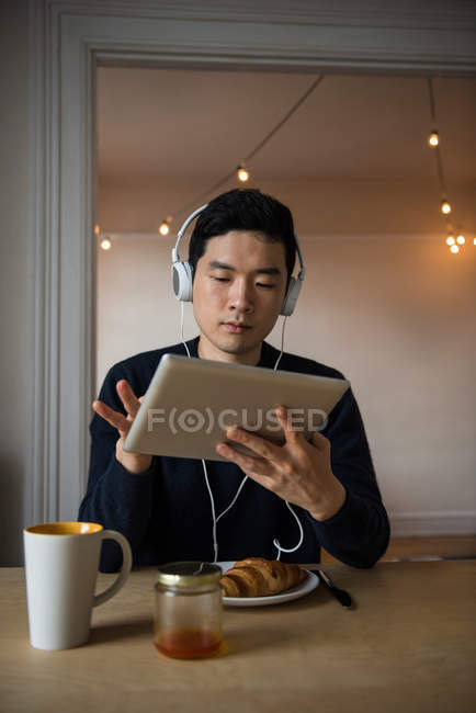 Человек слушает музыку на цифровом планшете дома — стоковое фото