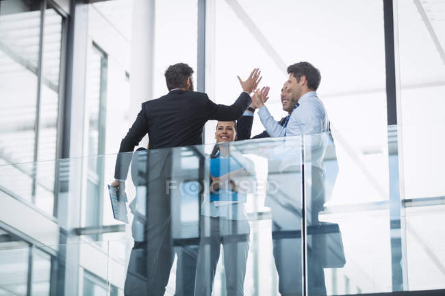 Group of business people giving high five inside office building — Stock Photo