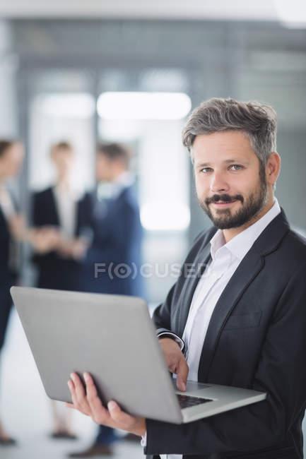Ritratto di un uomo d'affari in piedi in ufficio e utilizzando il computer portatile — Foto stock