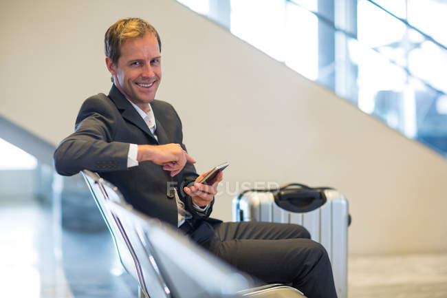 Portrait of smiling businessman sitting with mobile phone in waiting area — Stock Photo