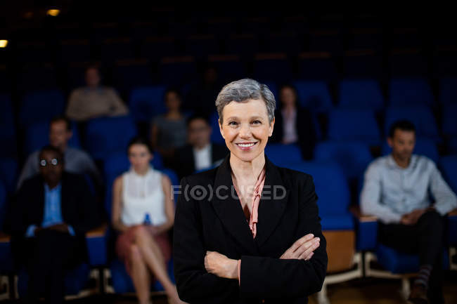 Portrait of female business executive with arms crossed at conference center — Stock Photo