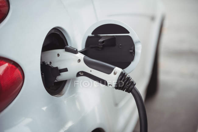 Gros plan de la voiture chargée avec un chargeur de voiture électrique à la station de charge — Photo de stock