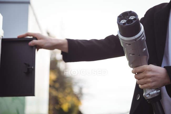 Mains de l'homme tenant le chargeur de voiture à la station de charge du véhicule électrique — Photo de stock