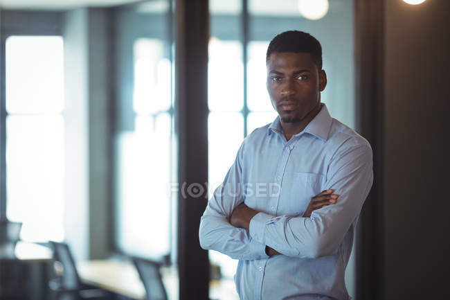 Portrait of businessman with arms crossed in office — Stock Photo