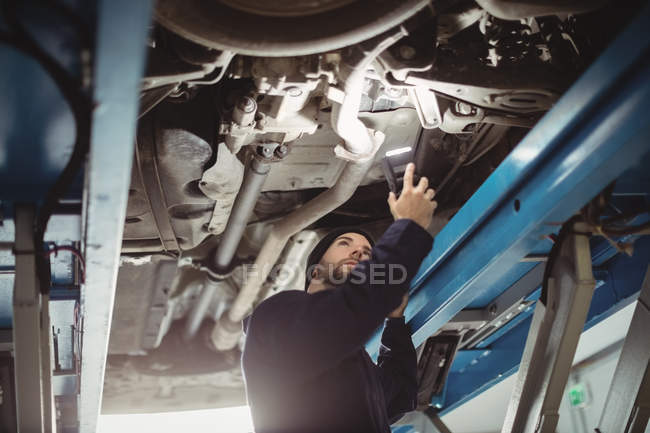mechanic examining a car with flashlight in repair garage vehicle