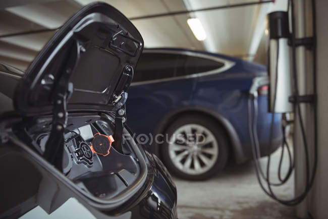 Close-up de tomada de combustível carro elétrico na garagem — Fotografia de Stock