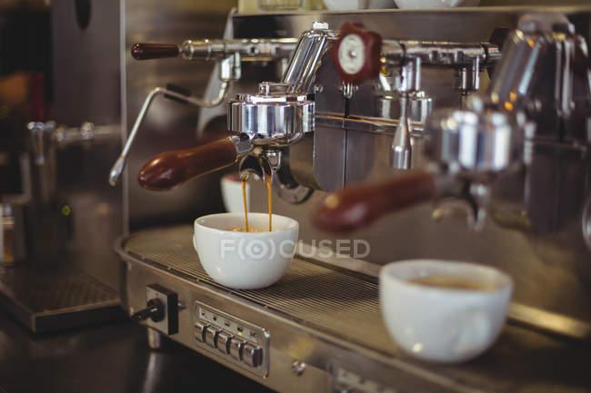 Закри еспресо ллється з кавомашину в кафе — стокове фото
