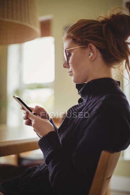 Чудова жінка вдома користується мобільним телефоном. — стокове фото
