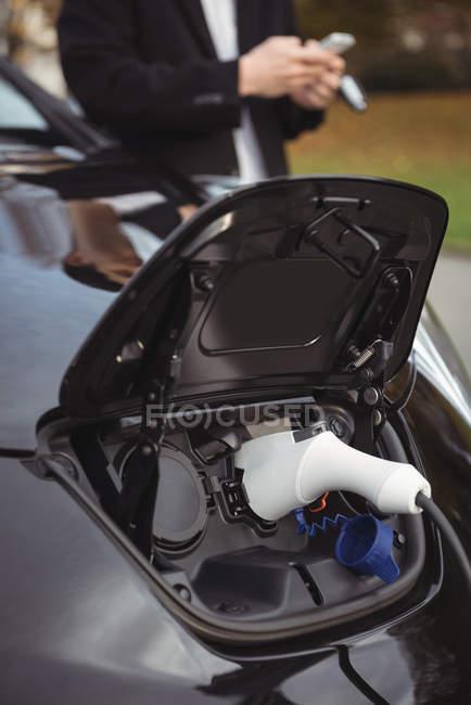 Gros plan de la voiture électrique chargée à la station de recharge — Photo de stock