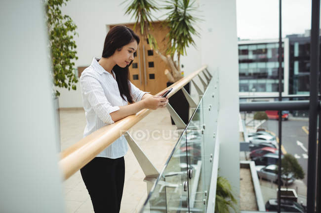 Side view of businesswoman using mobile phone at office balcony — Stock Photo
