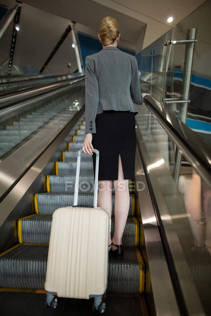 Rear view of businesswoman standing on escalator with luggage at airport — Stock Photo