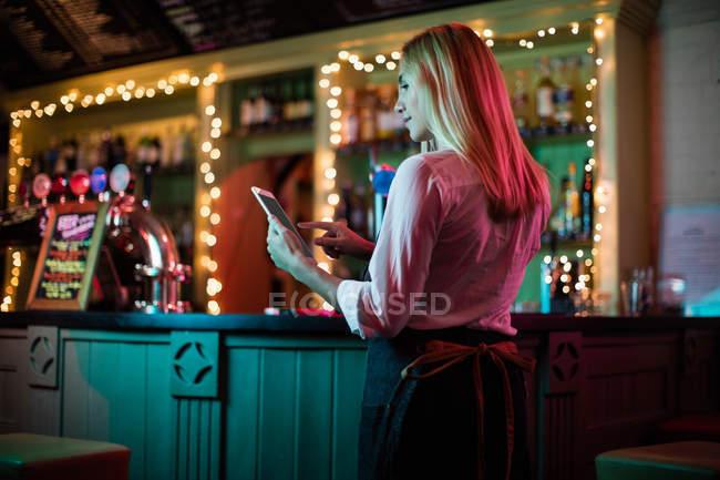 Beautiful waitress using a digital tablet in bar — Stock Photo
