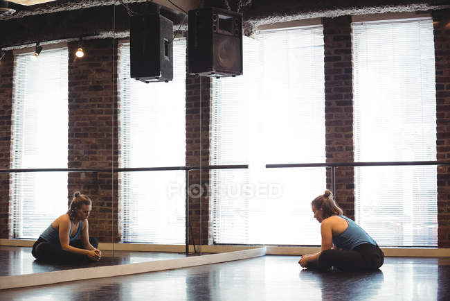 Young female dancer performing stretching exercise in dance studio — Stock Photo
