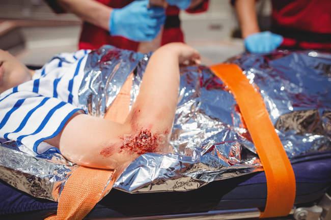 Sanitäter untersuchen verletzten Jungen auf Straße — Stockfoto