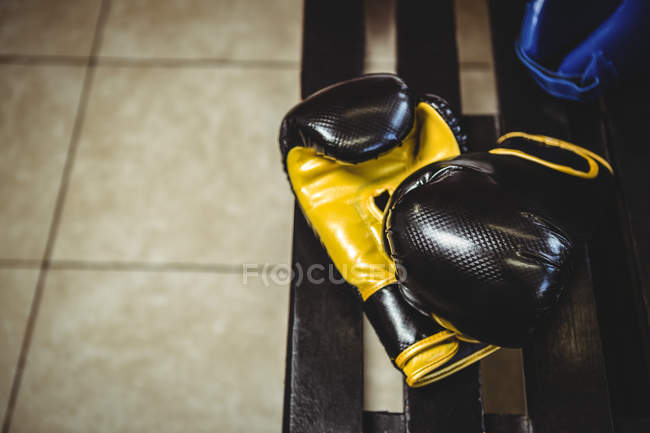 Close-up de luvas de boxe no banco no vestiário — Fotografia de Stock