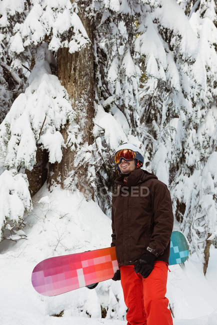 Man standing and holding a snowboard on snow covered mountain — Fotografia de Stock