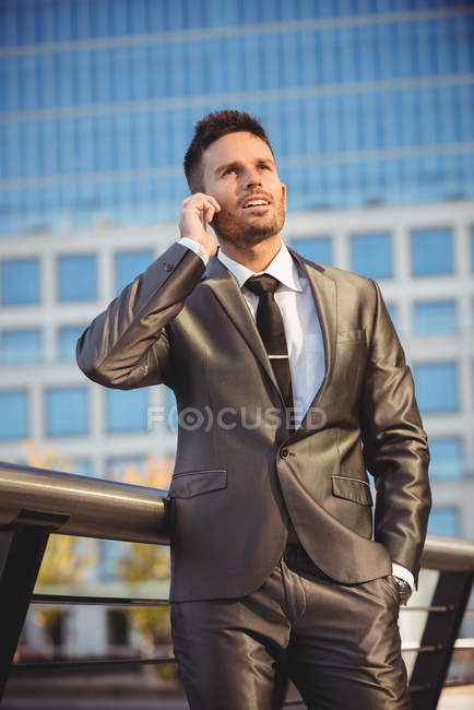 Businessman talking on mobile phone near office building — Stock Photo