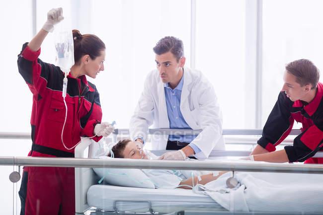 Medici che visitano il paziente in corridoio in ospedale — Foto stock