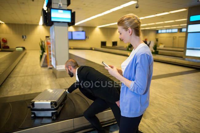 Человек, собирание чемодан на ленточный конвейер багажа во время женщина, с помощью мобильного телефона в терминал аэропорта — стоковое фото