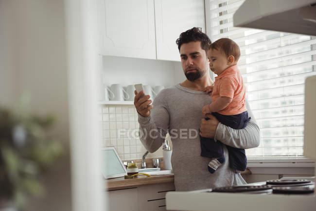 Отец использует мобильный телефон, держа ребенка на кухне дома — стоковое фото