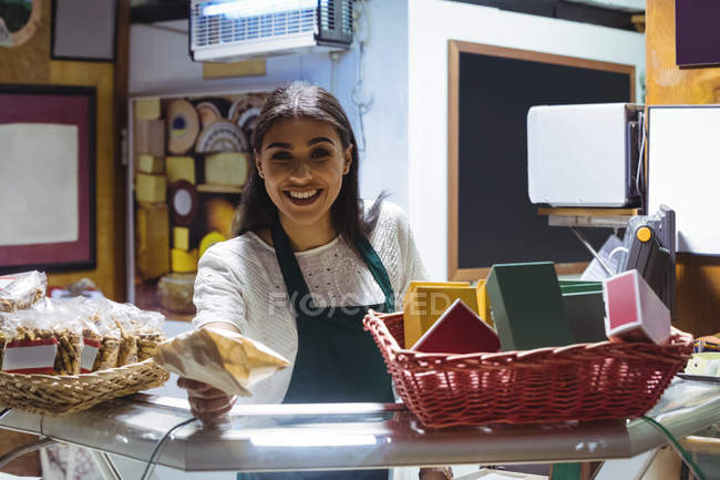 Smiling waitress giving parcel at counter in cafe — Stock Photo