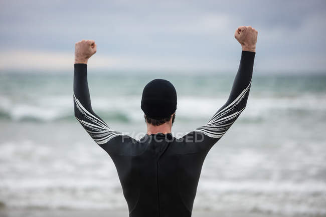 Rear view of athlete in wet suit standing with arms up on beach — Stock Photo