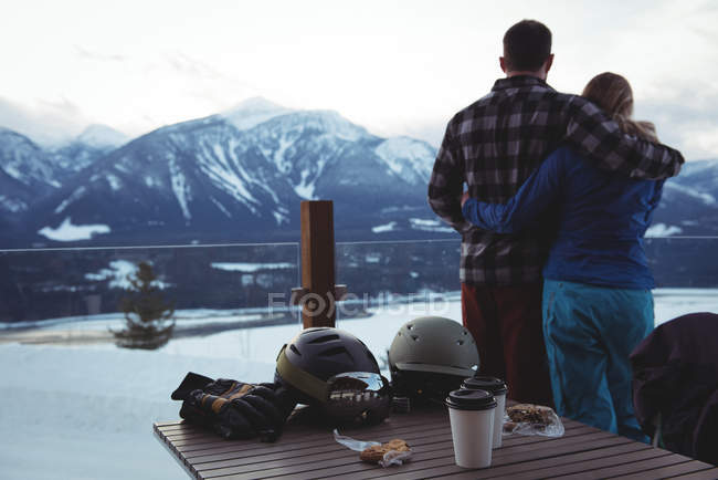Rear view of couple embracing against snow capped mountains — Stock Photo