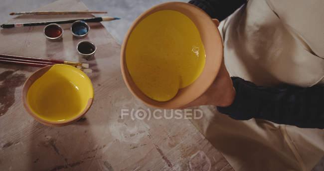 Potter segurando tigela de cerâmica na oficina de cerâmica — Fotografia de Stock